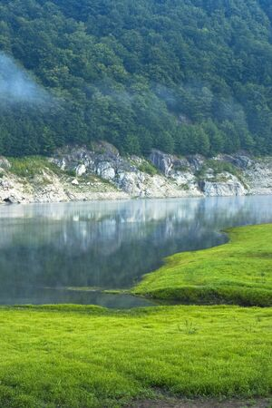 a lake at the mountains, green grass and morning fog Stock Photo - 9313359