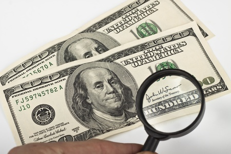 magnifying a dollar bill with a magnifying glass on white background Stock Photo - 9313392
