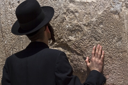jewish religious man praying at the western wall with one hand on the wall photo