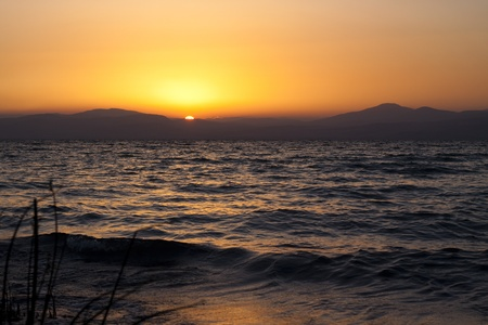 sunset over the mountain  and the sun reflecting the sea Stock Photo - 9309724