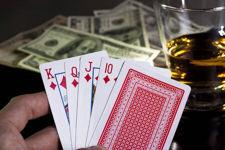 poker playing cards dollars and a whiskey glass