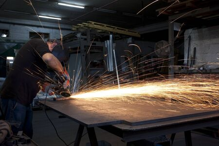proffesional heavy industry worker with all the safety equipment grinding metal with flying sparks all arround Stock Photo - 9313344