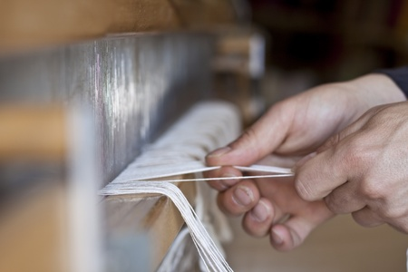 cotton wool: hand working with white strings in the txtile industry
