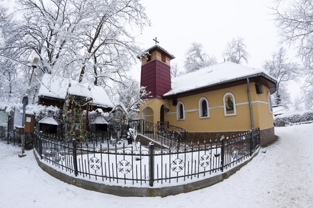a small ortodox church covered with snow in the winter photo