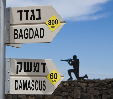bagdad damascus direction sign with a soldier in the background over blue sky Stock Photo