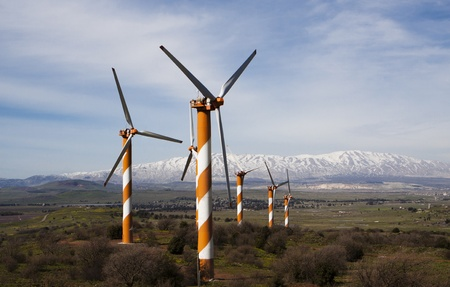 wind turbine farm on a hill with snow mountain peak in the background Stock Photo - 9310514
