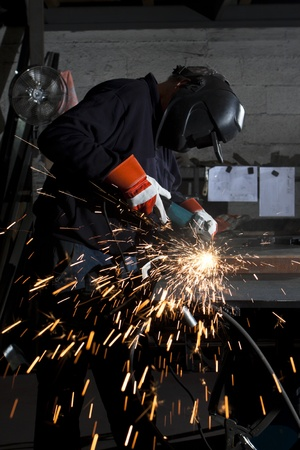 orange sparks during metal grinding in a steel factory photo