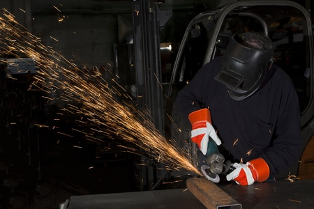 orange sparks during metal grinding in heavy industry plant photo