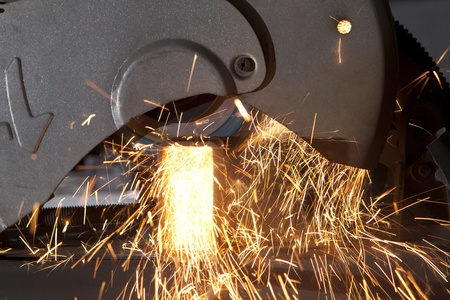 metal cutting saw throwing sparks all over photo