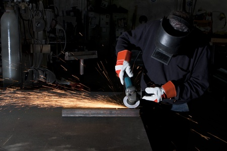 man working in a heawy industry workshop with a grinder spartks alying all over photo