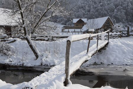a small bridge covered with white snow in a mountain village in eastern europe Stock Photo