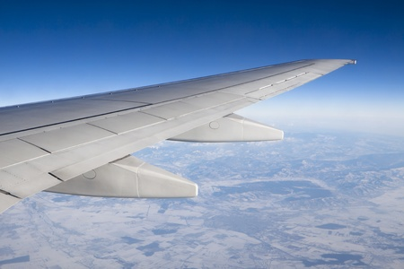 airplane wing in the air trough the window with terestrial view and blue sky Stock Photo