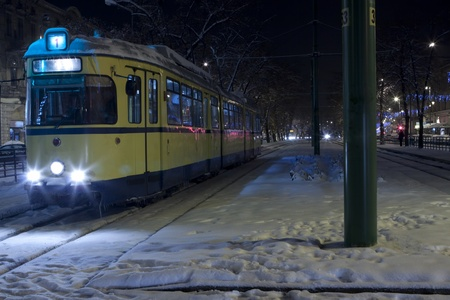 tramline: yellow tram in a cold winter night with snow and ice on it