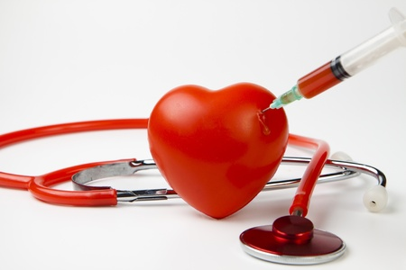 medical bills: blood drop while injecting red heart with syringe on white background