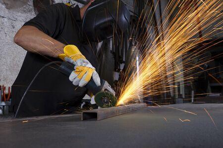afilador: Sparks volando sobre la mesa de trabajo en metal pulido