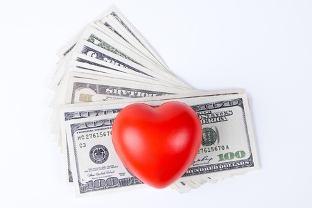 red  heart on top of dollars white background photo