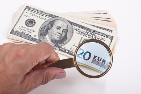 magnifying a hundred dollar bill with golden color loupe showing 20 euro bill on white background photo