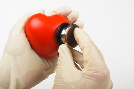 examining red heart hold in hand with a stethoscope on white background