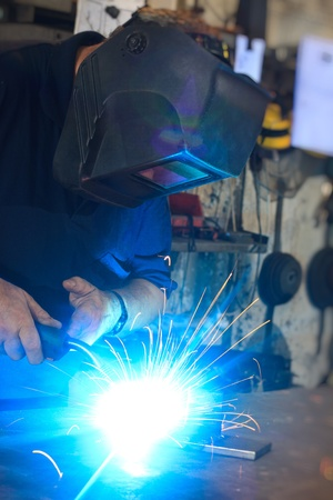 welder working with metal in a heawy industry workshop photo