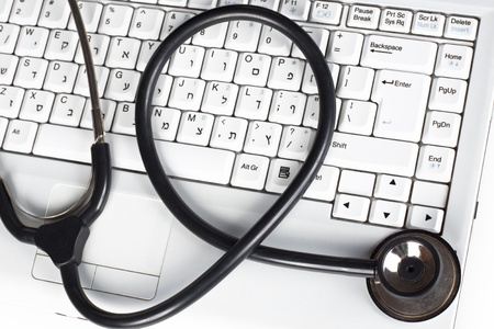 Laptop keyboard closeup with a black stethoscope