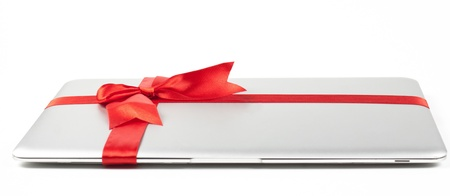 closed silver laptop gift with red ribbon isolated on white background photo
