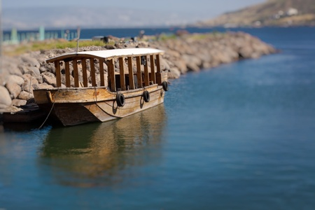 Single ancient boat on the see of galilee with reflection in the water
