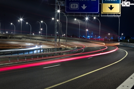 light trails on a highway passing vehicles light and road sign Stock Photo