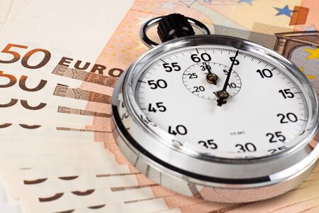 silver color old stopwatch on top of 50 euro banknotes photo