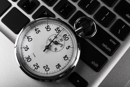 Silver stopwatch on silver laptop  keyboard closeup Stock Photo