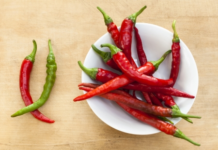 Red chili with one green cilli pepper in a bowl on wood background photo
