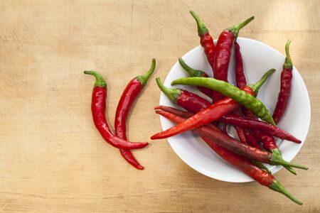 Red chili with one green cilli pepper in a bowl Two on wood background photo