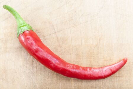 Single Red Hot Chili pepper on brown wood background photo