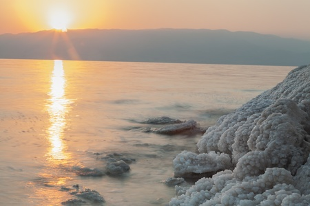 Sunrise in the dead sea with salt formations on the shore photo