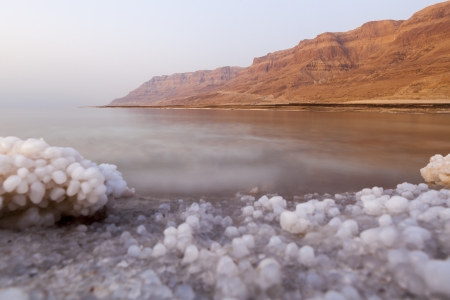 Dead sea lanscape with minehral structures on the shore and desert mountains in the background