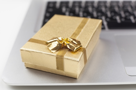 gold gift box on silver laptop closeup  photo