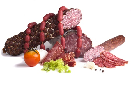 Various salami products in a with tomato isolated on white background