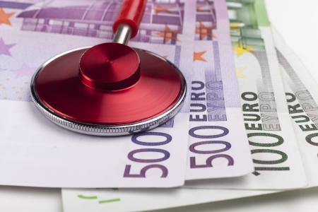 Red stethoscope close-up on top of euro bills