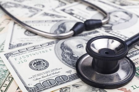 Black stethoscope close-up on top of Dollar banknotes side view photo