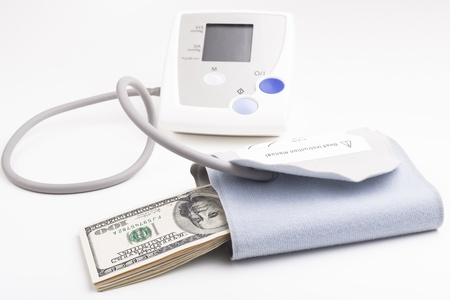 blood pressure bulb: Electronic blood pressure meter with dollar banknotes isolated on white background Stock Photo