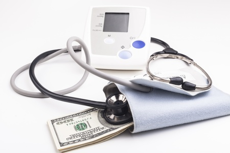 blood pressure bulb: Electronic blood pressure meter with dollar banknotes and stethoscope isolated on white background Stock Photo