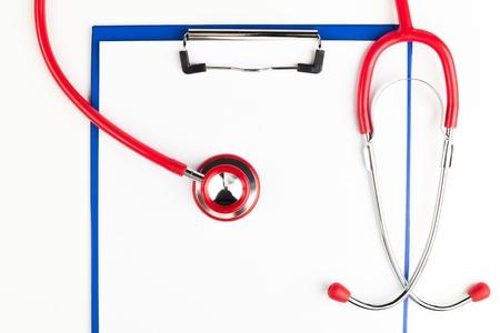 equipos medicos: Estetoscopio rojo sobre un cultivo portapapeles azul vac�o aislado en el fondo blanco Foto de archivo
