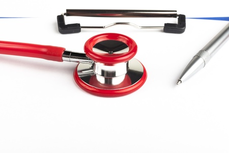 Red stethoscope on a empty  blue clipboard  close-up with silver colored pen photo