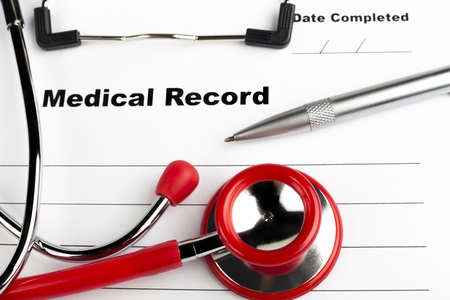 Red stethoscope on  blue clipboard  with medical record close-up with silver colored pen photo