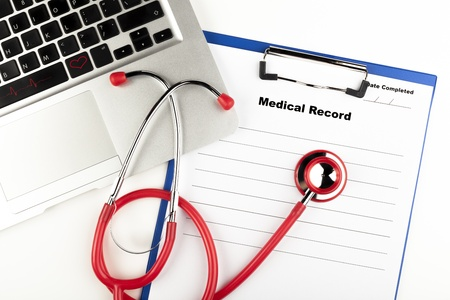 Red stethoscope on  blue clipboard  with medical record close-up with silver colored laptop