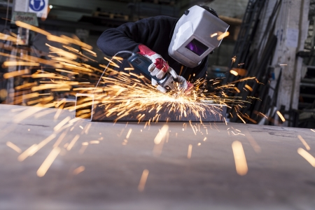 Metal industry worker grinding with mask on the face