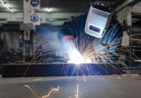 soldador: Soldadura con una gran cantidad de chispas en una fábrica de la industria de metal