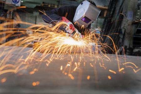 welding worker: Metal wroker in a factory grinding with sparks Stock Photo