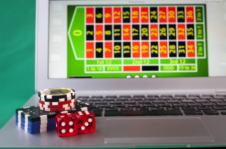 Dice and casino chips on silver color laptop conputer photo