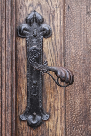 Ancient rusty church door handle on brown old wooden door photo
