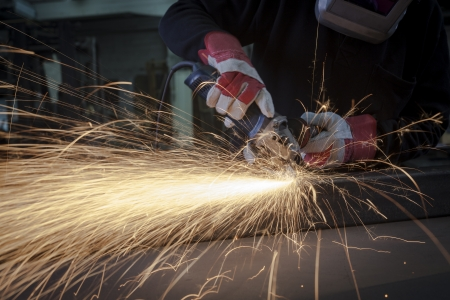 Grinding closeup with protection gloves and sparks